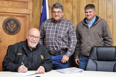 County Judge Joe Fauth is all smiles as he signs the contract with Collier Construction, LLC for the new $10,455,000 million justice center adjacent to the Grimes County Law Enforcement Center on FM 149 West. Michael Collier seals the deal with his signature while son and partner, Clayton Collier, looks on.